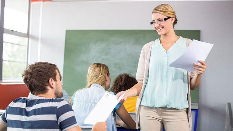 Lehrerin teilt Blätter aus